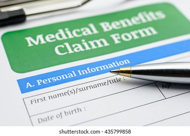 Blue ballpoint pen and a medical benefits claim form on a clip board. A form is waiting to be filled, checked, revised and signed by a patient, a physician and a nurse in a clinic / hospital.