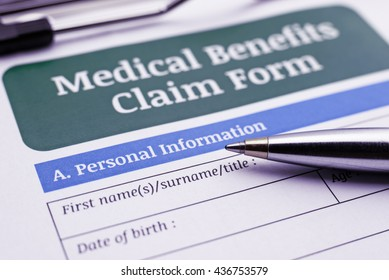 Blue ballpoint pen and a medical benefits claim form on a clipboard. A blank / empty form is waiting to be completed / filled and signed by a policyholder or an insured person.