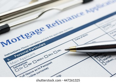 Blue ballpoint pen and a mortgage refinance application on a clipboard. A blank form is waiting to be filled / completed and signed by an applicant or a borrower who want to pay less interest rate.