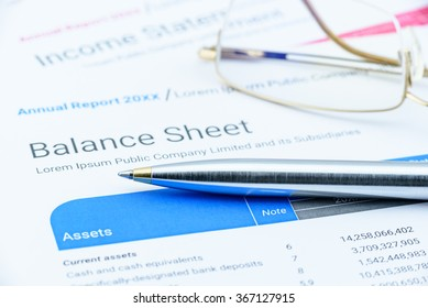 Blue ballpoint pen on a corporate balance sheet with eye glasses waiting for an auditor to audit before passing to executive committee in the boardroom. Financial and investment analysis concept.