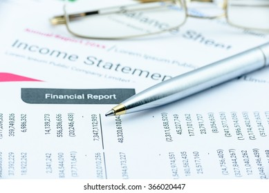 Blue ballpoint pen on a quarterly corporate financial report on a table waiting for the financial and investment analyst to analyse before public disclosure. Financial investment analysis concept.