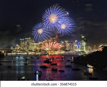 blue balls of New Year Fireworks in Sydney over city skyscrapers reflecting in still waters of Sydney harbour