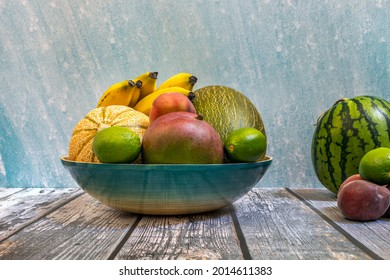 Blue bamboo tray with fresh seasonal fruits. Piel de sapo melons, mangoes and ripe bananas, peaches and watermelons.