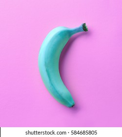 Blue banana on pink background. From top view