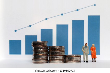 Blue bar graph with flow linear graph. The stack of coins and miniature older people. Concepts about increasing life expectancy and the lack of retirement funds.