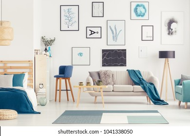 Blue bar stool next to a sofa with blanket near bed in open space interior with gallery of posters