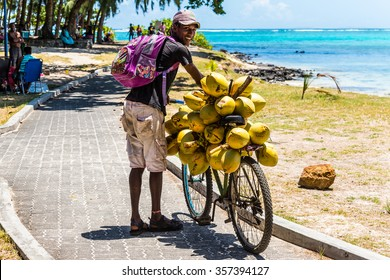 BLUE BAY, MAURITIUS - DECEMBER 27, 2015: Mauritius young man selling coconuts from his bike on the beach Blue Bay, Mauritius.
