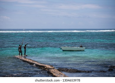 Blue Bay, Mauritius Island - 01.03.2019: Image of local people fishing along with tourists visiting the beautiful beaches of Mauritius.
