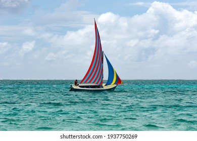 Blue Bay, Mauritius island - November 15, 2017: A colorful boat sails across the blue bay in a sunny day
