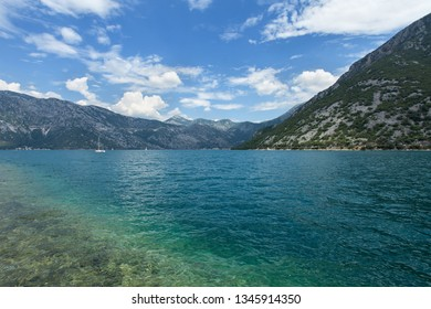 Blue bay of sea surrounded by rocky hills and mountains in the Adriatic sea on a clear summer day