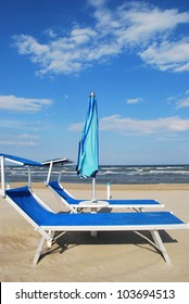 Blue beach chairs and umbrella, Rimini, Italy