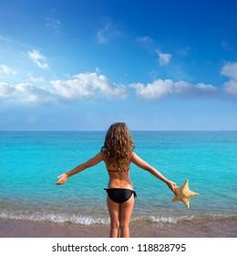 blue beach kid girl with bikini holding starfish looking sea in rear view