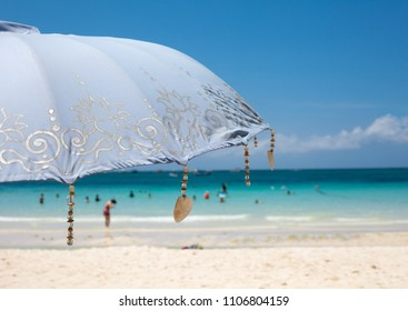 Blue beach umbrella with sea on the background, close-up