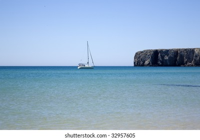 The blue beaches of southern Portugal, the Algarve. Martinhal beach in a summer morning, with a sailing ship passing by