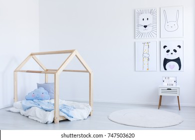 Blue bedsheets and pillows on wooden do it yourself bed in white boy's room with contrast color drawings