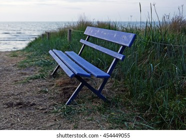 Blue bench in the dunes, sea in the background, evening, nobody