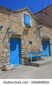 Blue bench front of old Croatian stone building with blue door and windows