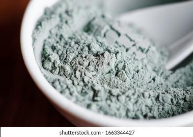 Blue bentonite clay powder in a bowl. Diy facial mask and body wrap recipe. Natural beauty treatment and spa. Clay texture close up, selective focus.