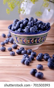Blue berries in a colorful bowl on wooden background.