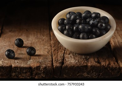 Blue Berries on a White marble Bowl on a wood table