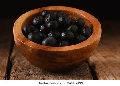 Blue Berries in a wooden bowl on a wood table