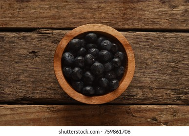 Blue Berries in a wooden bowl on a wood table from a top view