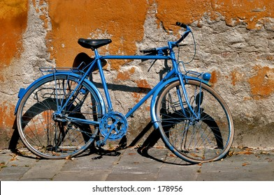 Blue bicycle against an orange wall