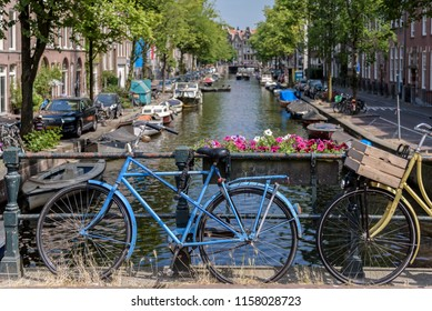 A blue bicycle alongside a canal in Amsterdam, on a sunny summers day.