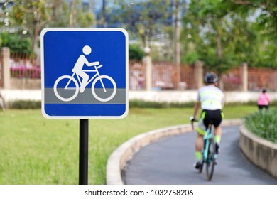 Blue bicycle lane sign with many people ride bike pass in public park. blur green tree background. Concept of healthy sports/Recreation.