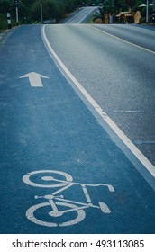 Blue bicycle lane signage on street, cinematic tone filter