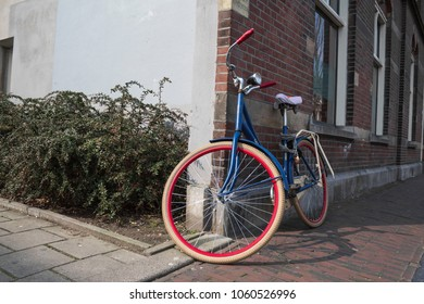 blue bicycle next to a wall of duch house with white and red  tires