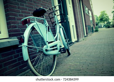 Blue bicycle parked near the house. Dutch lifestyle. City bikes in Netherlands. Sport life style. Riding.