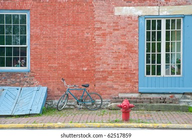 A blue bicycle parked on the cobblestone sidewalk between the painted windows of an antique store, the aged red bricks and the red fire hydrant create an  interesting composition.