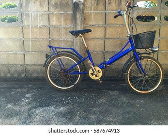 blue Bicycle for women is beside a cement block fence.