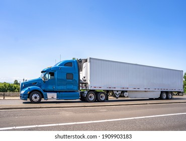 Blue big rig industrial grade bonnet long hauler diesel semi truck with high roof cab and refrigerator semi trailer running with commercial cargo on the wide highway road with green trees hillside