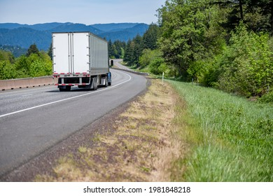 Blue big rig industrial semi truck tractor with roof spoiler transporting cargo in dry van semi trailer running on curving highway road with green forest trees and mountain in Columbia Gorge