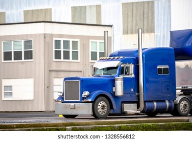 Blue big rig long haul semi truck with high cab and semi trailer stand on warehouse parking lot waiting for loading and possibility of continuing to the destination according to approved schedule