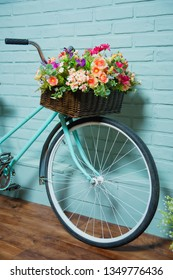 Blue bike on brick wall background. Summer photo zone in the Studio. Wicker basket with artificial flowers on the bike.