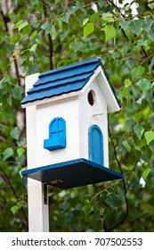 Blue birdhouse on the tree. Wooden house for birds among the leaves