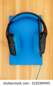 Blue and black headset with microphone with a book on a wood desk