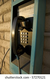 blue and black pay phone on white brick wall