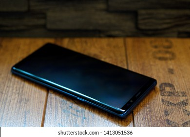 Blue / black smartphone with pen on wood  background