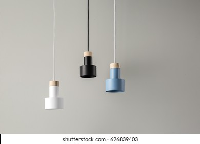Blue, black and white lamps with light wooden parts are hanging on the cables on the background of the gray wall. Closeup. Horizontal.