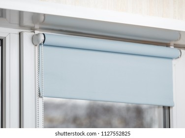 Blue blackout roller blind on the white plastic window. Shutters on the plastic window.