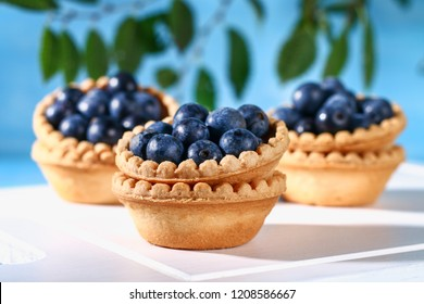 Blue blackthorn berries in sand tartlets on a table.