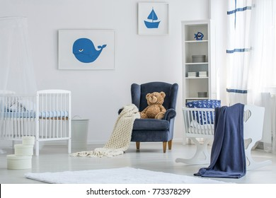 Blue blanket on cradle and teddy bear on armchair in white baby's bedroom with marine posters