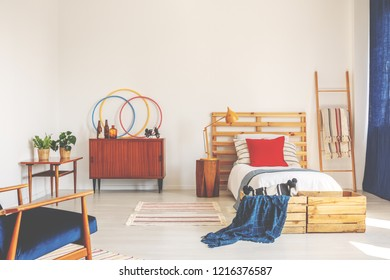 Blue blanket and red cushion on wooden bed in bedroom interior with cabinet and plants. Real photo