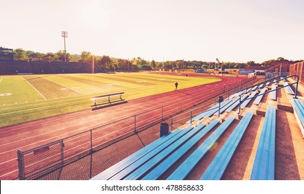 Blue bleachers in a large outdoor sports stadium