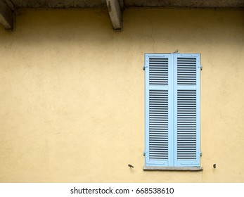 A blue blind over brown wall