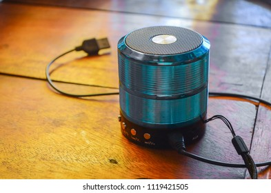 Blue Bluetooth speakers are placed on a gold-brown wooden desk. The sun is shining down in the morning.